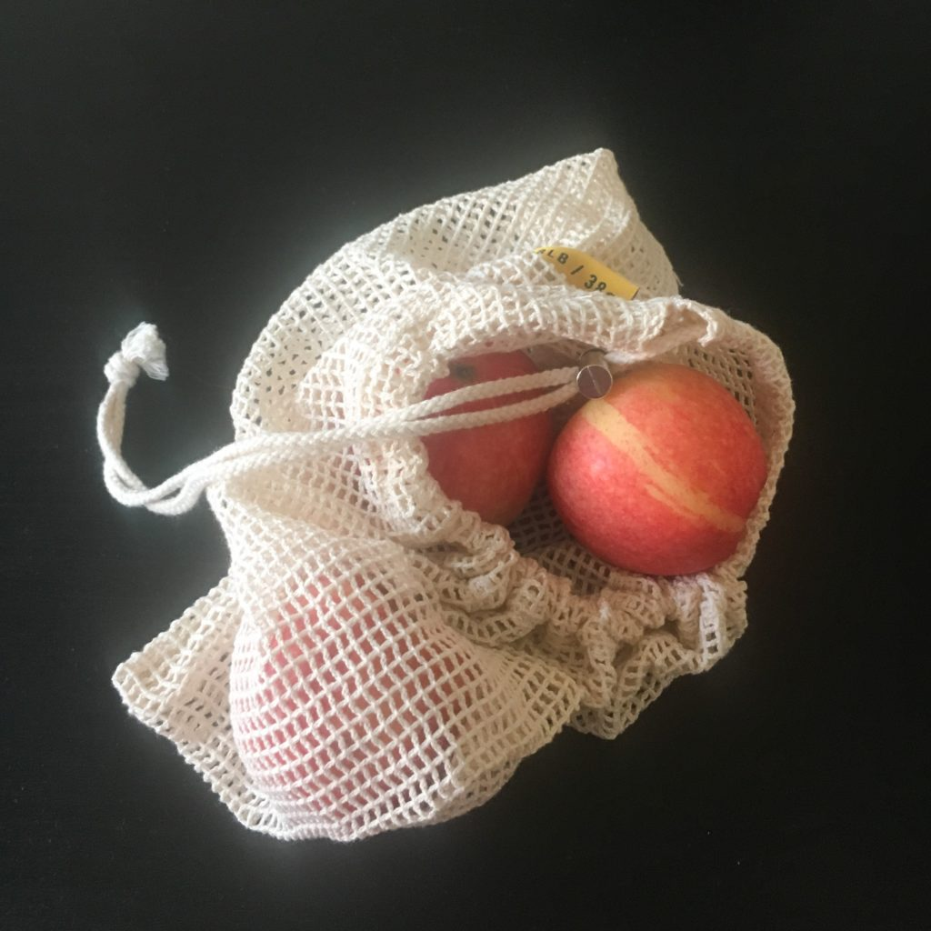 red apples in reusable cotton bag