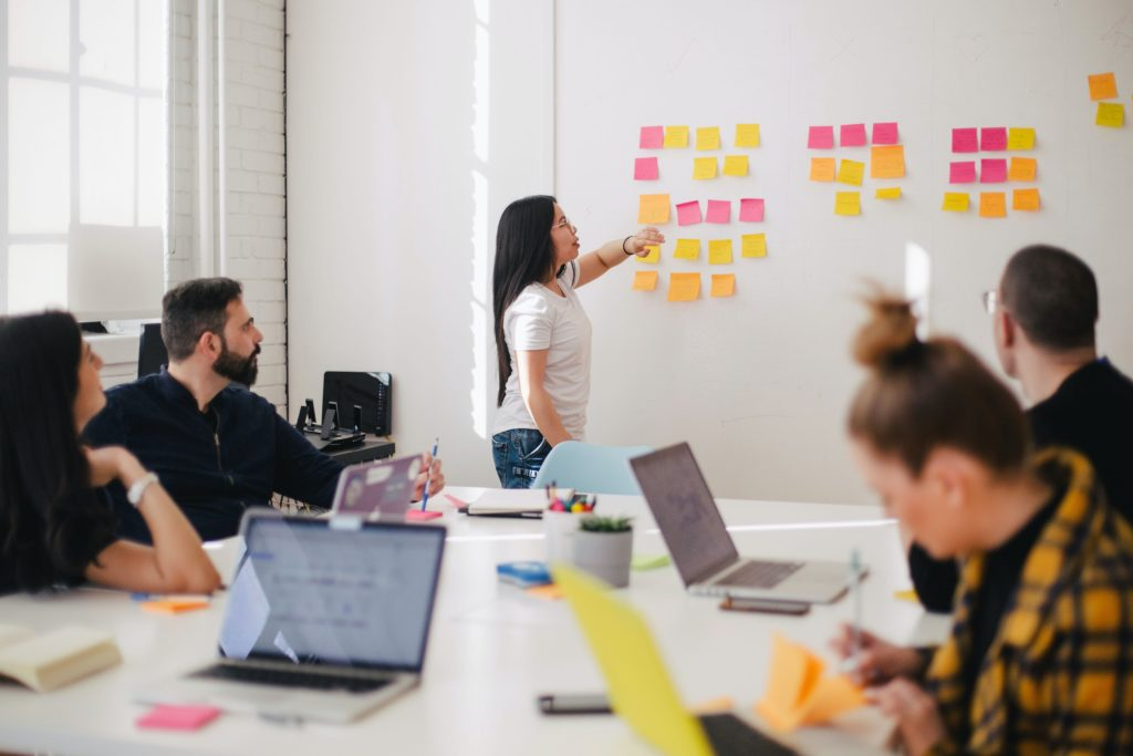 Woman leading meeting with sticky notes on the wall.